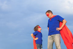 Father and son playing superhero at the day time. People having fun outdoors. Concept of friendly family Stock Photography