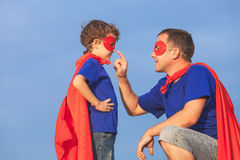 Father and son playing superhero at the day time. People having fun outdoors. Concept of friendly family Royalty Free Stock Images