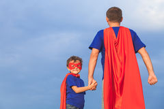 Father and son playing superhero at the day time. People having fun outdoors. Concept of friendly family Stock Images