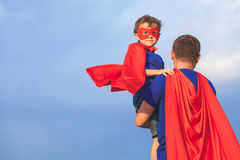 Father and son playing superhero at the day time. People having fun outdoors. Concept of friendly family Stock Image