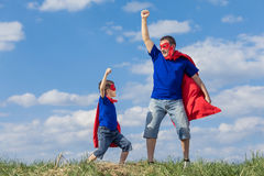 Father and son playing superhero at the day time. People having fun outdoors. Concept of friendly family Stock Photos