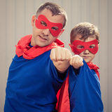 Father and son playing superhero outdoors at the day time. Father and son playing superhero  at the day time. People having fun outdoors. Concept of friendly Royalty Free Stock Photos
