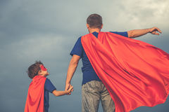 Father and son playing superhero outdoors at the day time. Father and son playing superhero at the day time. People having fun outdoors. Concept of friendly Royalty Free Stock Photo