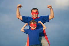 Father and son playing superhero outdoors at the day time. Father and son playing superhero at the day time. People having fun outdoors. Concept of friendly Royalty Free Stock Photography