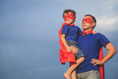 Father and son playing superhero outdoors at the day time. stock photo