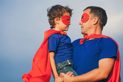 Father and son playing superhero outdoors at the day time. Father and son playing superhero at the day time. People having fun outdoors. Concept of friendly Stock Image