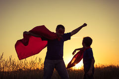 Father and son playing superhero at the sunset time. People having fun outdoors. Concept of friendly family Stock Photo