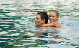 Father and Son Playing In A Swimming Pool royalty free stock photography