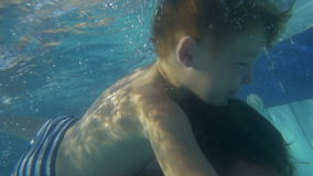 Father and son playing in the swimming pool stock video footage