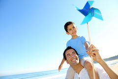 Father and son playing with swirl. Little boy up on his fathers's shoulders holding swirl Stock Photography