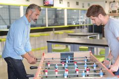 Father and son playing table football. Activity royalty free stock image