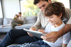Father and son playing with tablet royalty free stock image