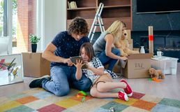 Father and son playing the tablet. While the mother unpacks moving boxes royalty free stock photo