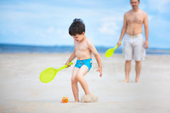 Father and son playing tennis on the beach Stock Photography
