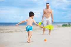 Father and son playing tennis on the beach Royalty Free Stock Photo