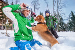 Father with son playing with their dog in deep snow Stock Images