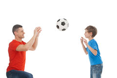 Father and son playing together. Cheerful father and son playing with ball together while isolated on white stock photos