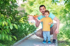 Father and son playing together outdoors in summer day: dad and child are launching toy airplane. New start, parental help concept stock image
