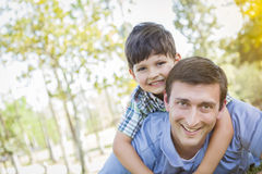 Father and Son Playing Together in the Park. Mixed Race Father and Son Playing Together in the Park Royalty Free Stock Image