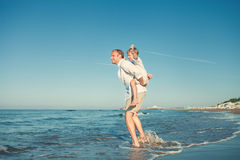 Father with son playing together on sea surf line stock image