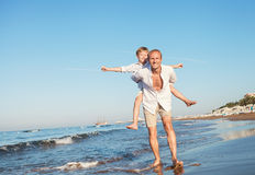 Father with son playing together on the sea surf line Royalty Free Stock Photos