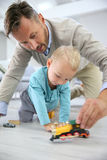 Father and son playing with toy cars on the floor Stock Photos