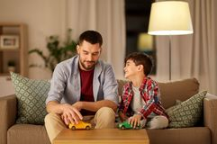 Father and son playing with toy cars at home. Family, fatherhood and people concept - happy father and son playing with toy cars at home in evening stock images