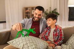 Father and son playing with toy dinosaur at home. Family, fatherhood and people concept - happy father and son playing with toy dinosaur at home stock image