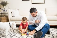 Father And Son Playing With Toys By Puppy At Home. Mid adult men spending leisure time with son while playing with toys by puppy at home stock image