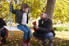 Father With Son Playing On Tree Swing In Autumn Garden Stock Image