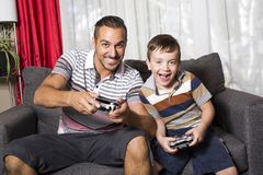 Father and son playing video game. A father and son playing in the living room stock photos