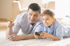 Father and son playing video game on floor at home Stock Photography