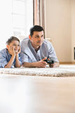 Father and son playing video game on floor at home Royalty Free Stock Photos