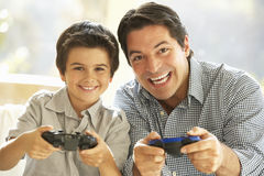 Father And Son Playing Video Game At Home stock image