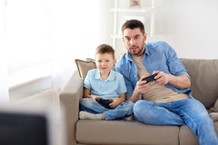 Father and son playing video game at home. Family, fatherhood and people concept - happy father and little son with gamepads playing video game at home Royalty Free Stock Photo