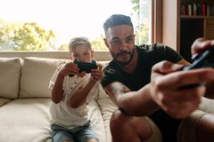Father and son playing video game at home. Young men and little boy sitting on sofa in living room and playing video game Royalty Free Stock Photos