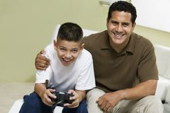 Father with Son Playing Video Game on sofa in living room portrait Royalty Free Stock Image