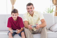 Father and son playing video game on sofa. Portrait of happy father and son playing video game on sofa at home Royalty Free Stock Photography