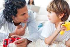 Father and son playing video games. Lying on the floor with mother in the background Stock Photography
