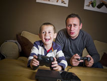 Father and son playing Video Games. Sitting in the Sofa Stock Image