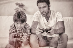 Father and son playing video games. On the couch Royalty Free Stock Image