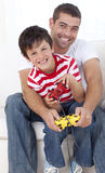 Father and son playing video games at home. Happy father and son playing video games at home Royalty Free Stock Photos
