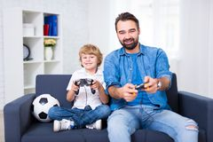 Father and son playing video games at home. Happy father and son playing video games at home stock photo