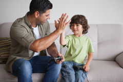 Father and son playing video games in living room. Cheerful father and son playing video games in the living room at home Stock Images