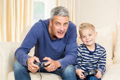 Father and son playing video games. On the sofa royalty free stock photography