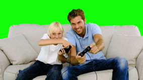 Father and son playing video games on the sofa on green screen