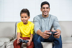 Father and son playing video games on the sofa Stock Photography