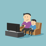 Father and son playing video games on sofa. Playful father and son spending time together and playing video games on a game console in living room at home. Great Royalty Free Stock Photo