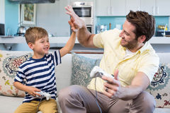 Father and son playing video games together. At home in the living room stock images