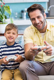 Father and son playing video games together. At home in the living room royalty free stock photos